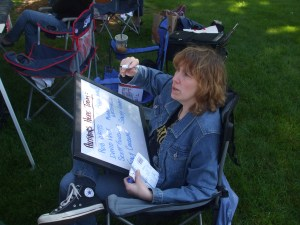 Author Stacey Longo writing out all the names of the authors appearing at the craft show