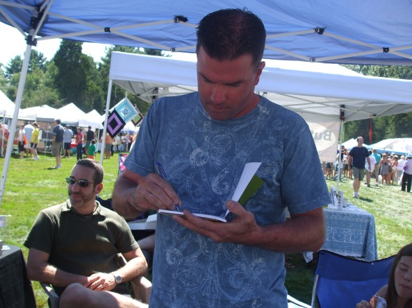 Author Rob Watts autographing his novel, Huldufólk, for a fan. Photo by Jason Harris.
