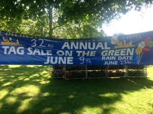 BB, the Books & Boos mascot hovering around the banner for the 32nd Annual Tag Sale on the Green