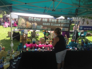 Christine Volpe arranging pieces of work at the Glow in the Dark Glass tent.