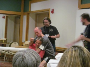 Author P. Gardner Goldsmith having some fun as he shaves some of Rio Youers' head as Author James Moore films it.