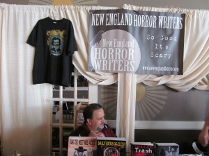 The New England Horror Writers table with author Scott Goudsward sitting behind it.