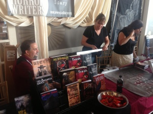 Author Stacey Longo (middle)helping author Tracy Carbone (right) with her banner as author Scott Goudsward looks on.
