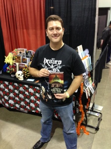 Author Gordon Bean holding his book, Dawn of Broken Glass, at the New England Horror Writers booth.