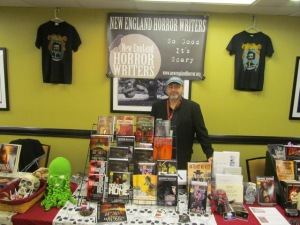 Author T.T. Zuma behind the New England Horror Wrters' table.