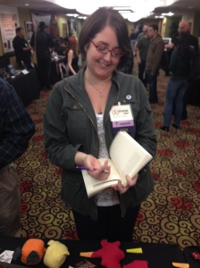 Author Catherine Grant signing a copy of Wicked Seasons.