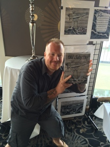 Artist and author Seth McCombs holding his book, Old Salty Dog.