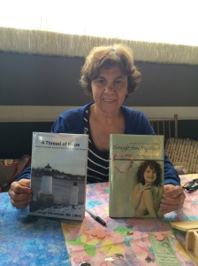 Author Jacqui DeLorenzo with her two books, A Thread of Hope and Straight from My Heart.