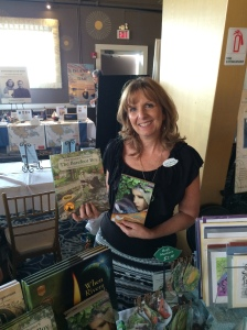 Artist/Illustrator Lisa Greenleaf holding up some of her work.