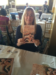 Author Karen Ann holding her book, Of Blood and Lions.