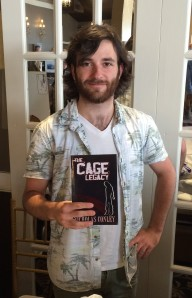 Author Nicholas Conley with his book, The Cage Legacy.